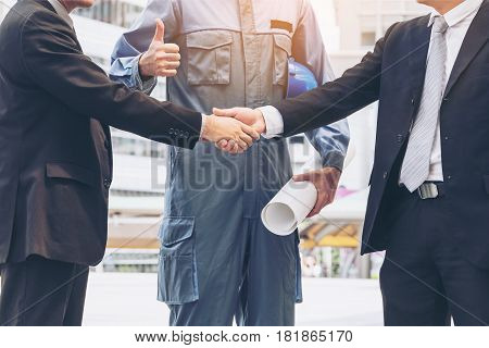 Businessmen Handshake With Engineer Thumbs Up