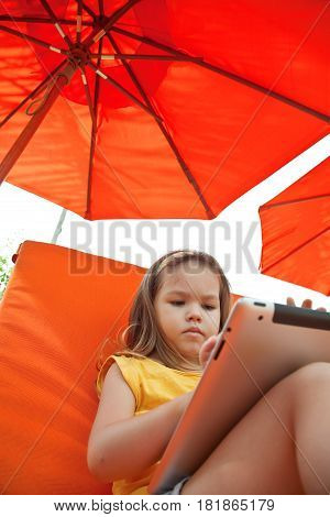 Toddler asian girl using tablet pc outdoors