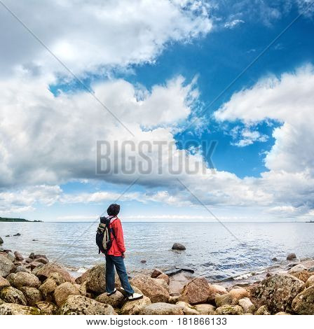 A tourist looks into the distance on a background of sea horizon and the beautiful clouds