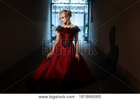 Woman in a Victorian manner dressed in a red dress.