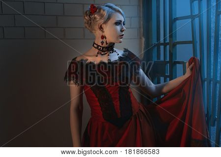 Beautiful woman in a Victorian style wearing a lush red dress and ornaments.