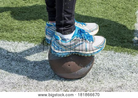 An athlete shows his balance standing on a medicine ball