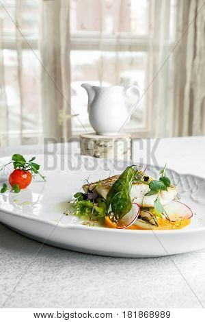 Fish dish - fillet of zander in plate on the table near window, served with tomato, radish and milk sauce