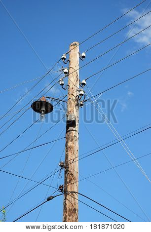 Old wooden electric post power pole. Power line. Wooden Utility Pole with light Bulb.