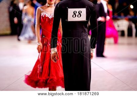 male dancer athlete in black tailcoat and woman dancer in red ball gown