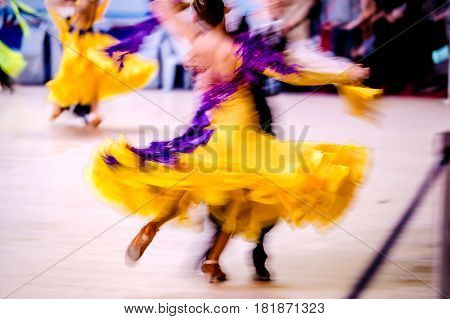 blurred couple athletes dancers competition in ballroom dancing