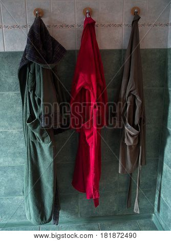 Three bathrobes hanging in the bathroom On hooks