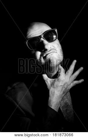 Portrait of gangster in sunglasses, black background