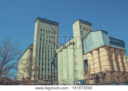 Vintage grain elevator against a blue sky. Agriculture in Russia.