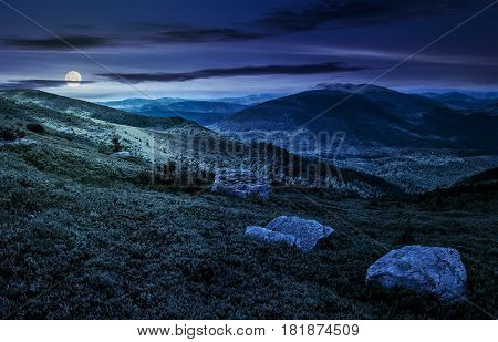 huge stones among the grass on top of the hillside meadow near the edge of a mountain. vivid summer landscape at night in full moon light
