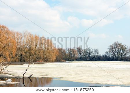 Early spring, melting snow and ice, the forest lake is freed of ice