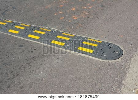 Traffic safety speed bump on an asphalt road. Speed bumps (or speed breakers).