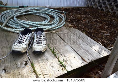footwear shoes on wooden decking with mulch and a garden hose