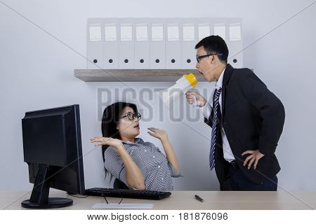 Portrait of a male manager shouting at his employee through megaphone while standing in the offi