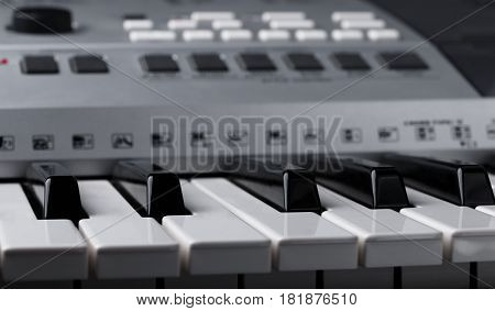 closeup fragment of electronic synthesizer keyboard with control buttons. selective focus