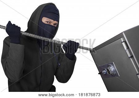 Photo of a male burglar using a crowbar to steal and open a safe-deposit box isolated on white background