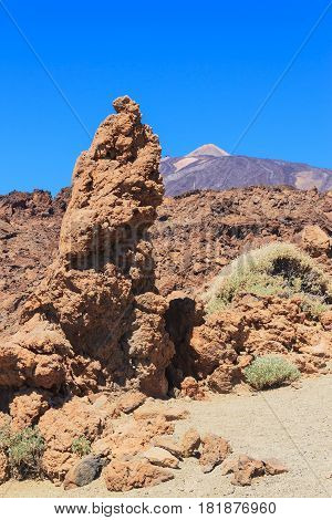 Red rock and volcano in the background. Blue sky. Pico del Teide Teide National park Tenerife Spain. No people