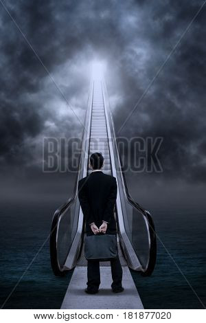 Back view of male entrepreneur looking at escalator on the ocean