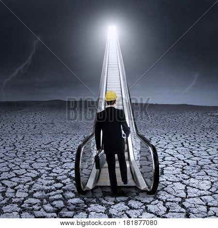 Young businessman go up the escalator on the dry land