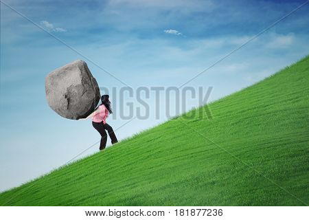 Young businesswoman climbing a hill while carrying a big stone on her back. Concept of hard work