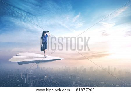 Young businesswoman standing on a paper aircraft and flying above a city while looking through binoculars