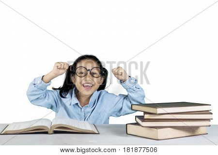 Portrait of cheerful girl celebrating her success while sitting in front of her book on table isolated on white background