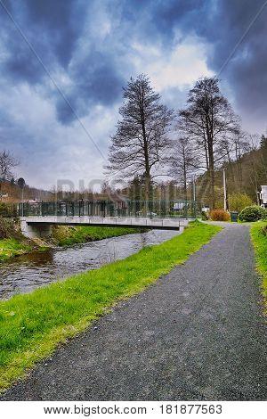 Srbska Kamenice, Czech Republic - April 08, 2017: Gravel Path Leading To Small Bridge Over Creek Kam