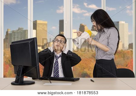 Young female employee is screaming at her manager through megaphone while working in the office with autumn background on the window