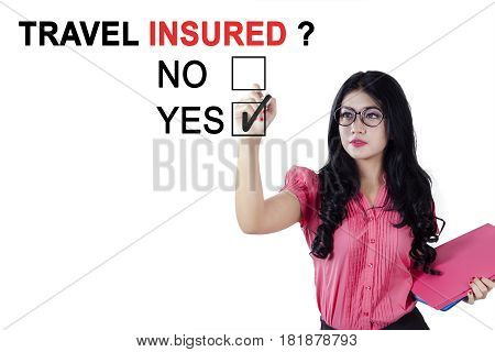 Female entrepreneur holding a pen and document while agreeing about travel insured