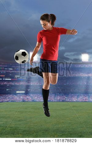 Young woman playing soccer inside stadium