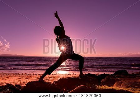a woman practicing yoga silhouetted at sunset on a Maui beach