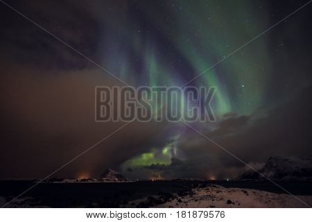 Amazing multicolored Aurora Borealis also know as Northern Lights in the night sky over Lofoten landscape Norway Scandinavia.