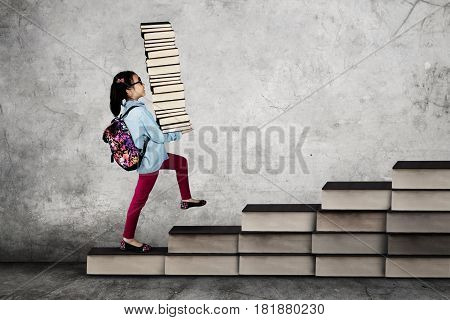 Photo of a female elementary school student walking on the stair made of book while carrying a stack of book