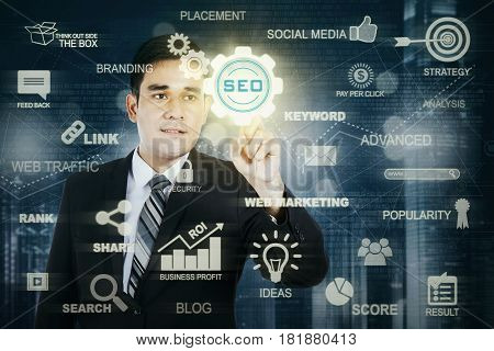 Photo of a male entrepreneur pressing a virtual SEO button on the futuristic screen. SEO concept