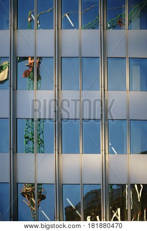 The irregular reflection of a crane in a modern facade of mirror windows.