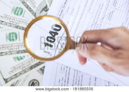 Hands of a man holding a magnifying glass while looking at numbers 1040 on the tax form