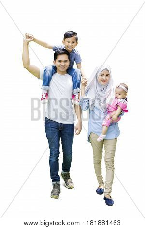 Full length of muslim family walking in the studio while the father carrying his son on shoulder
