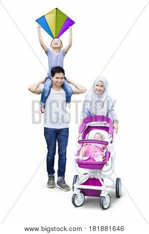 Two muslim parents smiling at the camera with their son holding a kite and the baby in a pram