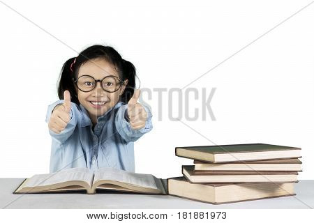 Portrait of primary student showing ok gesture with book on the table isolated on white background