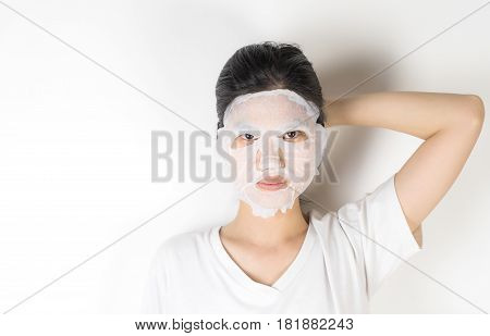 Asian girl in putting on a skin care paper mask