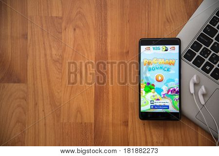 Los Angeles, USA, april 16, 2017: Pac man bounce application on smartphone with earphones and notebook on wooden background.