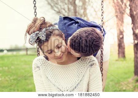 Young Couple Of Boyfriends Are Kissing On The Swing