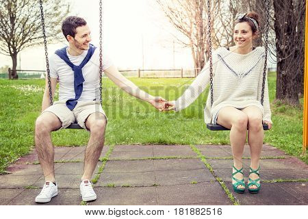 Pair Of Young Lovers Hand In Hand On The Swing