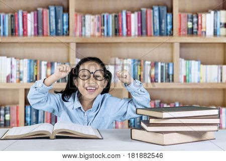 Portrait of successful student lifting her hands while sitting with book in the library