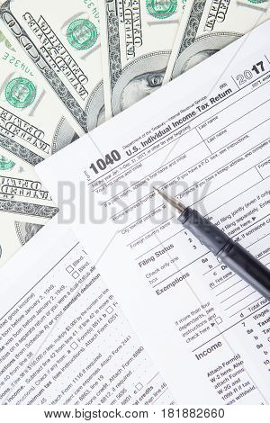 Closeup of pen on tax form with dollar money. tax return concept