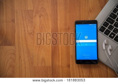 Los Angeles, USA, april 16, 2017: Wordpress application on smartphone with earphones and notebook on wooden background.