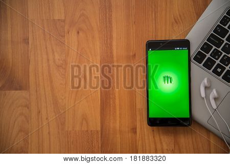 Los Angeles, USA, april 16, 2017: Pocketbook application on smartphone with earphones and notebook on wooden background.