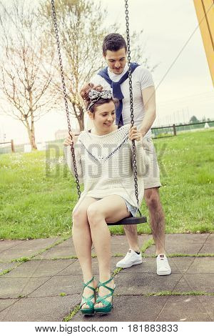 Young Man Pushes Her Girlfriend On The Swing