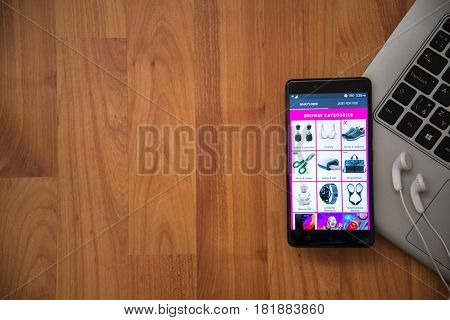 Los Angeles, USA, april 16, 2017: Aliexpress application on smartphone with earphones and notebook on wooden background.