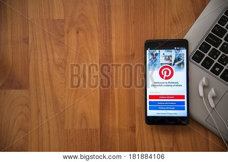Los Angeles, USA, april 16, 2017: Pinterest application on smartphone with earphones and notebook on wooden background.